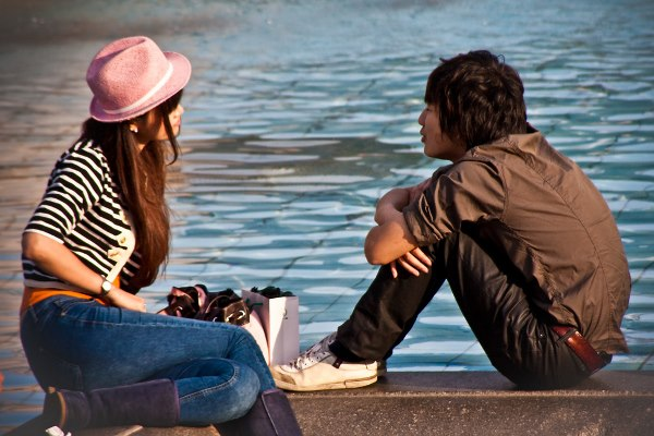 A teenage couple enjoy the sun by one of the Trafalgar Square fountains.